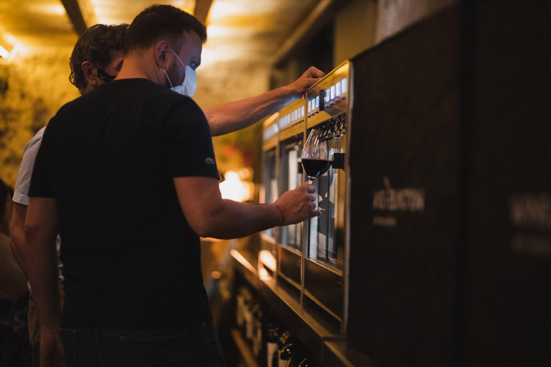 Personas utilizando las máquinas expendedoras de vinos del bar Vico Palermo.